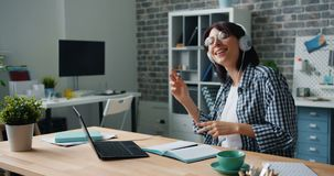 Female hipster having fun at work listening to music dancing typing on laptop. Female hipster attractive young lady is having fun at work listening to music stock video