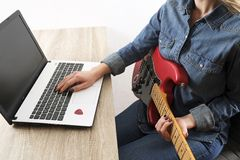 Casually dressed young woman with guitar playing songs in the room at home. Laptop on table. Online guitar lessons concept. Male g royalty free stock photography