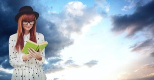 Female hipster reading book against sky Royalty Free Stock Images