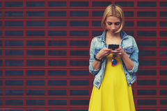 Female hipster student in the dress using mobile phone for connect to wireless Stock Photos