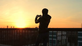 Female hipster taking photograph with cellphone of sunset cityscape roof view stock footage