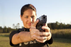 Female Hispanic Police Officer Aims Gun Stock Image