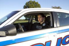 Female Hispanic Police Officer Checks Side Mirror Stock Photography