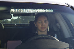 Female Hispanic Police Officer Looks into camera from Car Stock Image