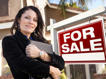 Female Hispanic Real Estate Agent, Sign and House Stock Image