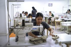 Female hispanic worker with sewing machine making alterations to clothes. stock photos