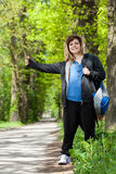 Female hitchhiker trying to catch the car Royalty Free Stock Image