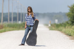 A Female Hitchhikes On A Dirt Road Royalty Free Stock Photo
