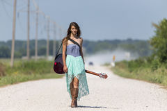 A Female Hitchhikes On A Dirt Road. Female walking down a dirt road hitchhiking with a guitar case Stock Photography