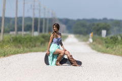 A Female Hitchhikes On A Dirt Road Royalty Free Stock Photography