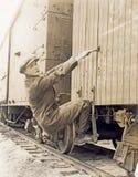 Female hobo climbing freight train Royalty Free Stock Image