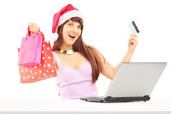 Female holding bags and doing online shopping through laptop and Royalty Free Stock Photos