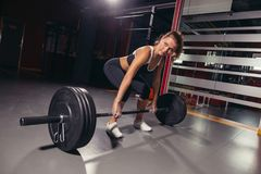 Female holding a barbell in her hands. Fit and attractive caucasian female holding barbell in her hands. concept of sport and healthy lifestyle Royalty Free Stock Photos