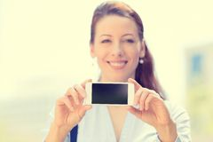 Female holding blank mobile smart phone, focus on black screen. Smiling female holding blank mobile smart phone isolated outside city background, focus on black Stock Photos