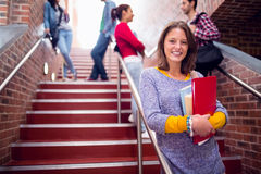 Female holding books with students on stairs in college. Portrait of a smiling female holding books with students behind on stairs in the college Stock Image