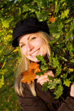 Female holding brown leafs. Blonde female holding brown leafs while surrounded by green leafs Stock Photos
