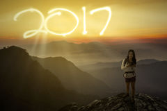 Female holding camera with number 2017 on cliff Stock Photos