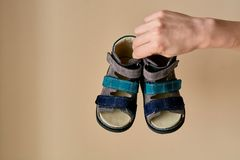 Female is holding close-up a special children`s orthopedic shoe sandals made of genuine leather. Comfortable shoes isolated on light background with copyspace royalty free stock photos