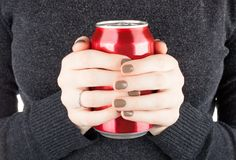 Female holding a closed can of soda. Woman holding a can of soda Royalty Free Stock Image