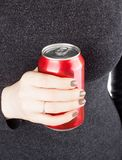 Female holding a closed can of soda. Woman holding a can of soda Stock Images