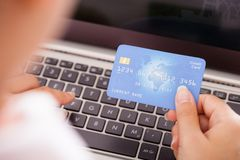 Female Holding Credit Card Over Keyboard Royalty Free Stock Photos