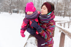 Female holding daughter in winter stock photos