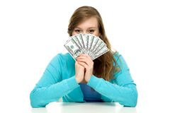 Female holding a fan of money over face Stock Photography