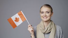 Female holding flag of Canada. Closeup portrait of young female holding small flag of Canada smiling at camera stock video footage