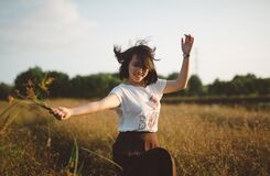 Female Holding Flowers Dancing in Field Stock Photo