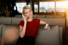 Female holding glass of water and phoning via smart phone while waiting for business lunch in modern cafe interior, Stock Images