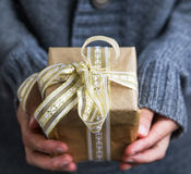 Female holding golden festive Christmas present decorated with r Royalty Free Stock Image