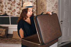 Female holding a half-open suitcase in her hands. Stock Image