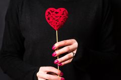 Female holding a heart shape wearing dark sweater. On black background stock photos