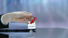 Female holding key from home with red ribbon, real estate purchase, dream house
