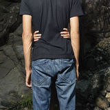 Female Holding Male Around Waist. Rear view of a male in jeans and black t-shirt embraced by woman beside rocks. Square format Stock Photo