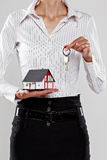 Female holding a model house and keys. On grey Stock Photos