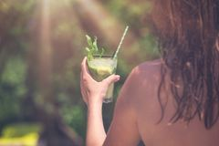 Female holding mojito cocktail outdoors stock photography