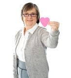 Female holding a pink paper heart. Focus on the heart stock images
