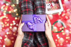Female holding a purple gift box Stock Images