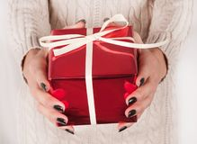 Female holding red gift box in hands with black nails and sweater Royalty Free Stock Photo