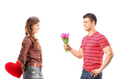 Female holding red heart behind and man giving flowers to her. Smiling female holding red heart behind and men giving bouquet of flowers to her isolated on white royalty free stock photography