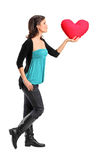 Female holding a red heart shaped pillow. Full length portrait of a female holding a red heart shaped pillow on white background royalty free stock photography
