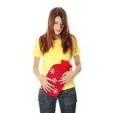 Female holding red hot water bottle. Or hot water bag on abdomen Stock Images