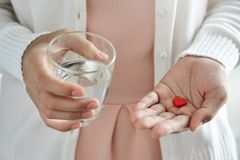 Female is holding red pills in heart shape. Female in white shirt is holding pills in heart shape and glass of water. Valentines concept. Love. Health. Disease royalty free stock photography