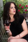 Female holding red wine glass in hand and relaxing in garden park stock photography