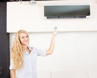 Female holding a remote control air conditioner royalty free stock image