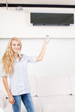 Female holding a remote control air conditioner Royalty Free Stock Photos