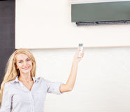 Female holding a remote control air conditioner Stock Image