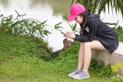 Female holding and see the smart phone in garden stock photo