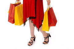 Female holding shopping bags. Waist and below view of a woman wearing red dress and black heels, holding multicolored shopping bags Stock Photo
